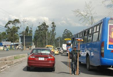 A broom salesman standing in the middle of the main route heading north out of Quito.