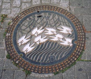 Industrialization Japanese-style: a beautiful crane motif on a sewage access cover in Himeji. (As it turns out, this is not a crane motif, but a flower motif -- Habenaria radiata; cf. the comment below.)