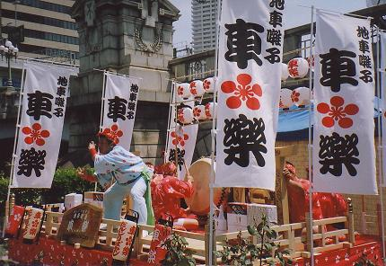 In the midst of the urban intensity of downtown Osaka, a traditional Japanese performance art exposition at a street fair.