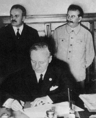 Ribbentrop signing the treaty while Molotov and Stalin watch.