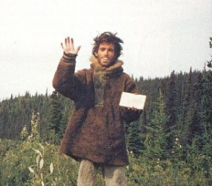 The last photographic self portrait of Chris McCandless, holding his farewell note and waving to the camera.