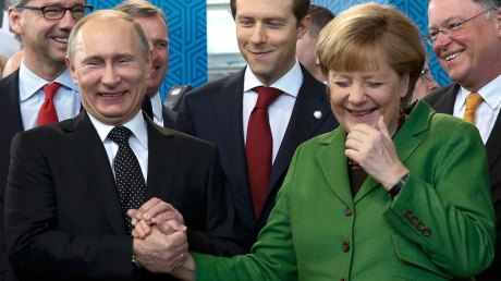 Russian President Putin holds hand of German Chancellor Merkel.